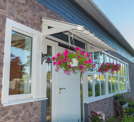 planters with flowers at the entrance to the house. Stock Photo