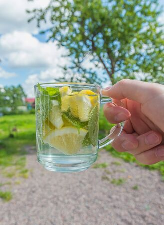in hand summer drink with lemon and mint.