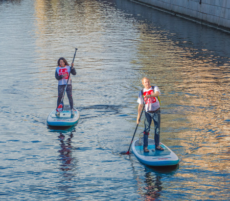 Russia, Saint-Petersburg, 14 August 2017 - SIP-surfing on the river floats a man and a woman.
