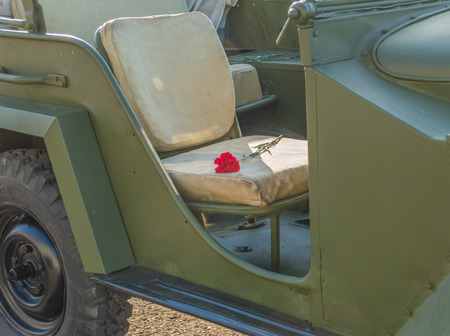 appointed: on the seat of the military car flowers red carnations, close-up.