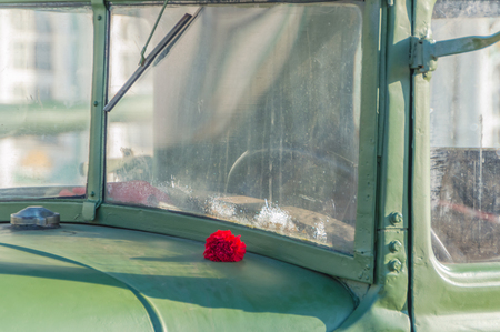 flowers red carnations on the windshield of a military vehicle. Stock Photo