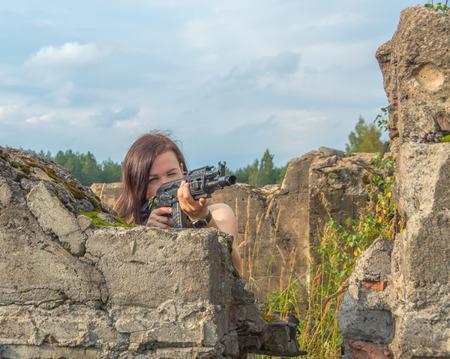 girl with a gun takes aim, standing behind a stone wall. closeup.