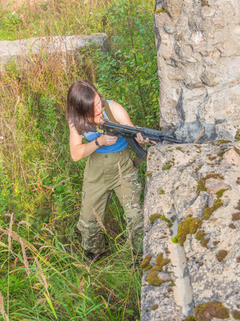 girl with a gun takes aim, standing behind a stone wall.