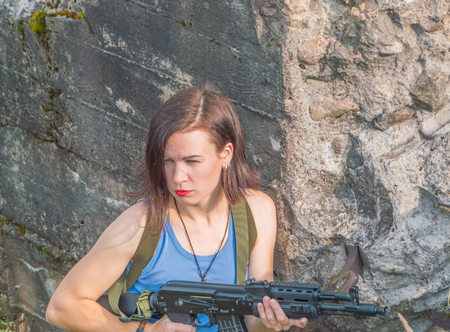 girl with a gun behind a stone wall. Stock Photo