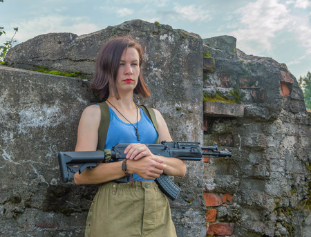 closeup of girl with gun posing by a concrete wall. Stock Photo