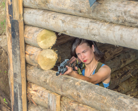 closeup of a girl with a gun in a wooden defensive cover. Stock Photo