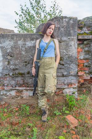 girl with gun posing in a stone wall. Stock Photo