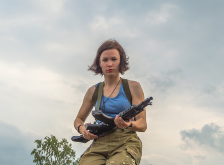 on the background of cloudy sky the girl with the weapon.