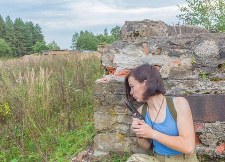 behind a concrete wall a girl with a gun is hiding. 版權商用圖片