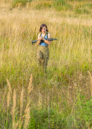 the meadow is a girl with a gun. Stock Photo