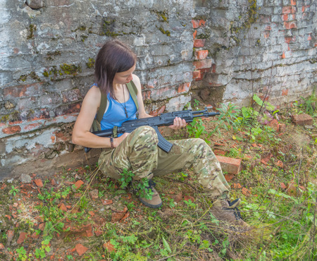 girl with a gun sitting in a stone wall. Фото со стока