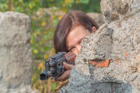 behind a concrete wall a girl with a gun takes aim, close-up.