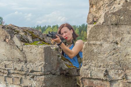 behind a concrete wall a girl with a gun takes aim.