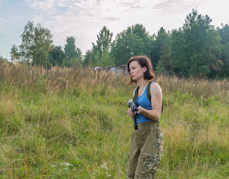 the girl with the gun is on the meadow.