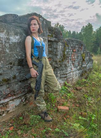 concrete wall posing girl with a gun.