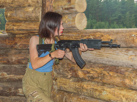 girl with a gun in a wooden defensive cover. Stock Photo - 86113240