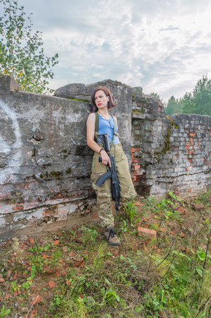 girl with gun posing standing at a concrete wall.