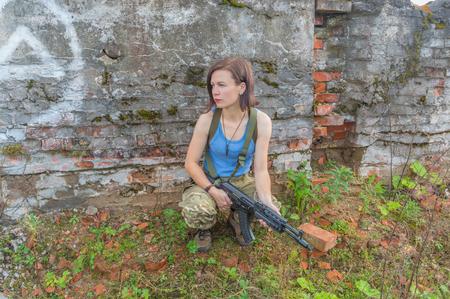 girl with a gun posing sitting in a stone wall.