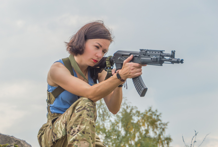 closeup of a girl aiming a gun.