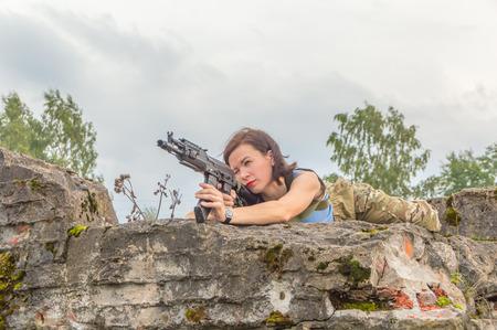 girl lying down aiming of a gun. Stock Photo
