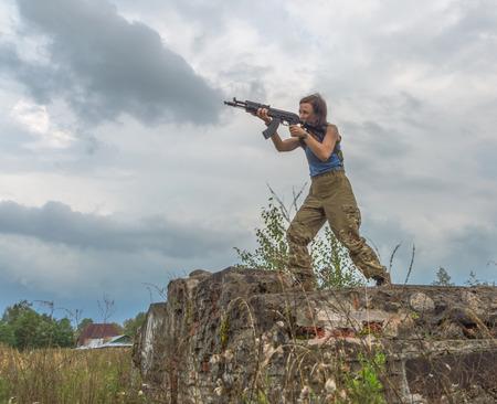 standing girl aiming a gun. Stock Photo