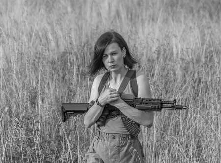black and white, in the girls hands the weapon is on the meadow.