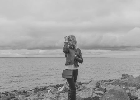 black and white, a beautiful woman stands on a rocky beach