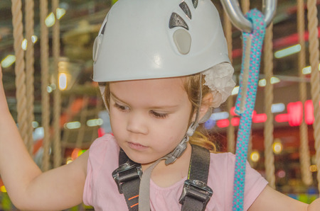 the girl in the insurance and wearing a helmet in the adventure Park, closeup
