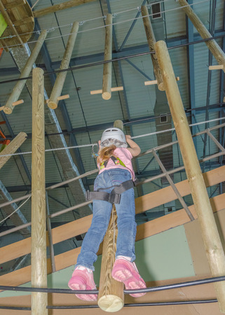 the girl in the white helmet in the adventure Park, overcomes obstacles