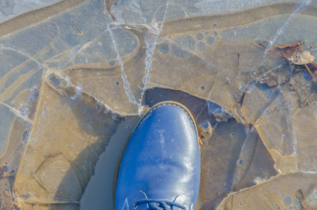 in a puddle of ice, a foot in the Shoe, closeup