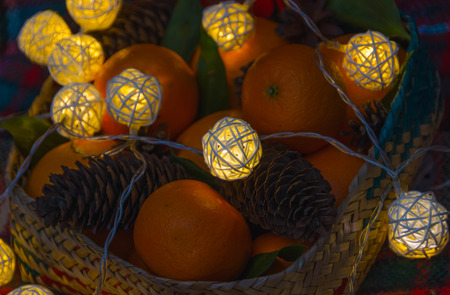 Cones, oranges and garland in a Christmas basket