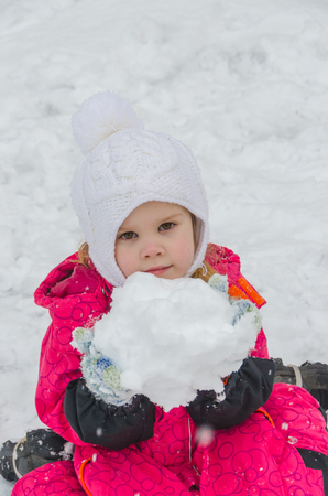 a girl sculpts a snowman in the Playground in winter