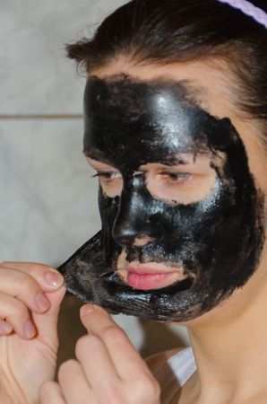 Girl with a black mask, cleansing of the skin