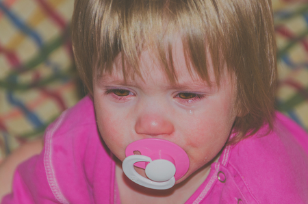 child close up with tears and a pacifier