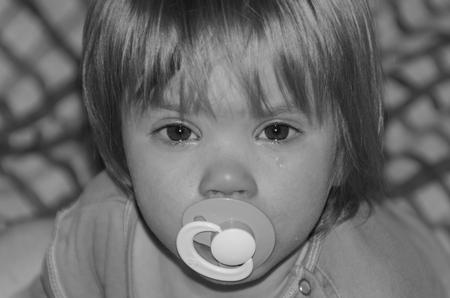 おしゃぶり泣いている赤ちゃん、眠りたくない 写真素材