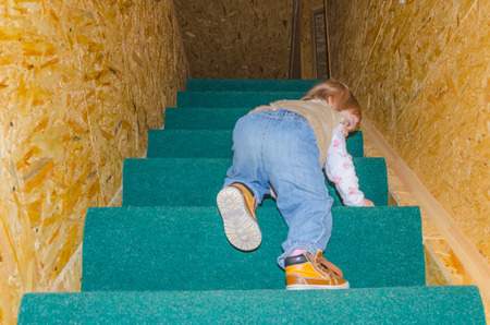 a child up the stairs in the house Stock Photo