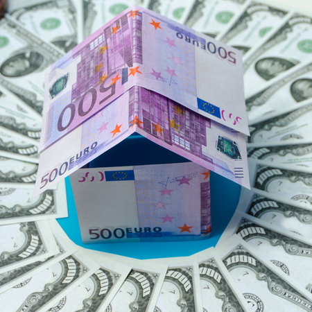 in the circle the dollar, a house made of Euro banknotes Stock Photo