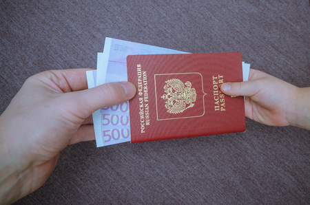 the child passes the passport with attached Euro Stock Photo