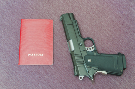 next to the pistol is a passport, on a fabric background Stock Photo
