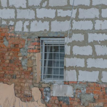 壊れた壁に棒が付いている窓 写真素材