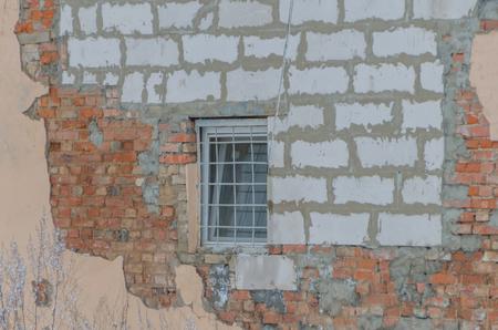 壊れた壁にバーのある窓