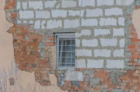 on the broken wall a window with bars Stock fotó