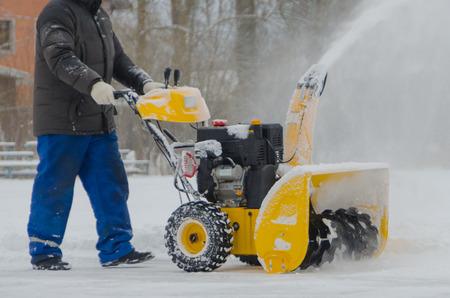 除雪車を持つ労働者は雪を取り除く 写真素材