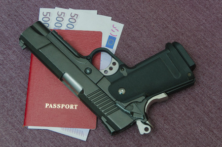 next to the pistol euros money invested in the passport Banco de Imagens