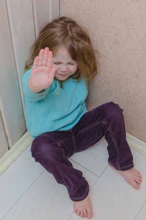 a child hides in the corner of the house, hand making a stop gesture, and social issues