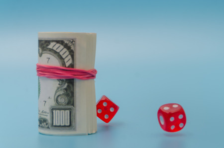 pack of dollars with dice on blue background