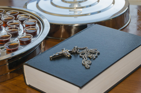 the communion wine and the Bible with a crucifix on the table