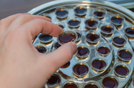 communion, hand takes a bowl of wine, close-up