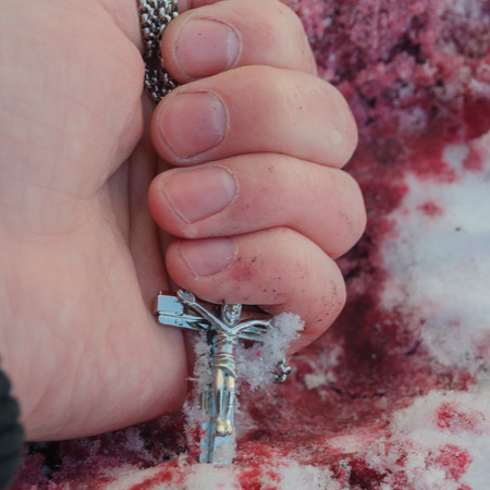 on the bloody snow hand of the killed man with the cross of the crucifixion Stockfoto - 95813007