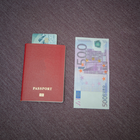 passport in which the credit card is attached to the table next to five hundred euros